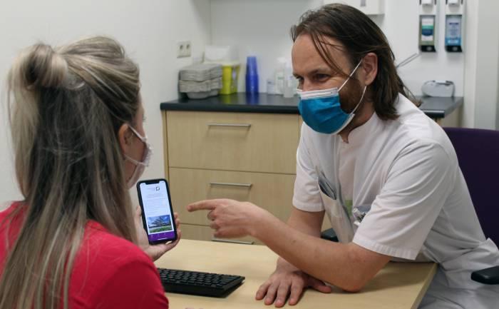 Arts-assistent toont Virtual Fracture Care app aan patiënt